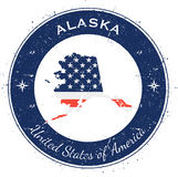 Alaska circular patriotic badge. Grunge rubber stamp with USA state flag, map and the Alaska written along circle border, vector illustration Stock Photos
