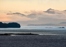 Alaska coast. Calm waters. Mountains shrouded in low clinging clouds and early morning mist Stock Photos