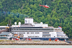 Alaska Cruise Ship Helicopter Tour. The Holland America Line Amsterdam cruise ship tied up at the Ore Dock in Skagway, Alaska, while a Temesco tour company royalty free stock photo