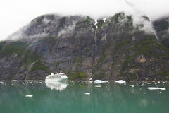 Alaska Cruise Ship Near Mountain with Clouds Stock Photo