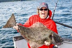 Alaska - glückliche Frau, die großen Heilbutt anhält lizenzfreies stockfoto