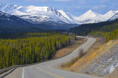 Alaska Highway, Yukon Territory, Canada. Scenic view of the Alaska Highway in the Yukon Territory, Canada, with snow covered mountains and conifer woods Stock Photography