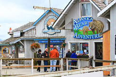 Alaska - Homer Bear Adventure Tours. A view of visitors and tourists checking out some of the bear viewing tour offices and gift shops along the world famous Stock Photos