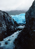 Alaska Ice A. Glacier meets black stone and feeds icy stream with misty mountains in the distance Stock Photo
