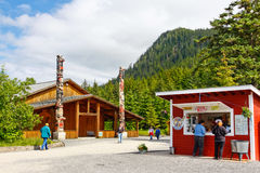 Alaska Icy Strait Point Attractions. In the foreground is a fun little donut, coffee and snack shop, while in the background two beautiful totem poles mark the Royalty Free Stock Image