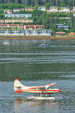 Alaska Juneau Waterfront Morning Rush Hour. A view of a De Havilland Otter bush float plane that just landed taxiing on the water, with a sailboat, small Royalty Free Stock Photo