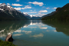 Alaska lake. Intense blue sky and still water surrounded by snow capped peaks Royalty Free Stock Images