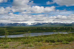 Alaska Landscape. A photo of an Alaskan landscape showing blue sky with clouds, a lake, snow covered mountains, and green fields Royalty Free Stock Images