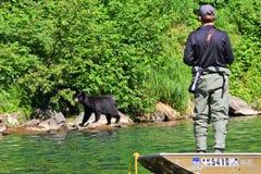 Alaska-Mann-Fischen-und Überwachenbär vom Boot Stockfotografie