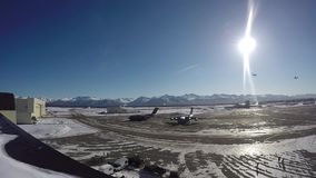 ALASKA, MARCH 2017, Two aircrafts fly curve over airport sun shine. US Air Force. Two C-130 transport aircraft fly a curve over an airport in Alaska stock video