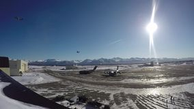 ALASKA, MARCH 2017, Two aircrafts fly curve over airport sun shine. US Air Force. Two C-130 transport aircraft fly a curve over an airport in Alaska stock footage
