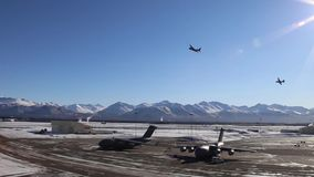 ALASKA, MARCH 2017, Two aircrafts fly curve over airport. US Air Force. Two C-130 transport aircraft fly a curve over an airport in Alaska stock video footage