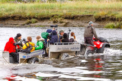 Alaska Photographers Riding ATV to go Brown Bear Viewing Silver Salmon Creek. A group of nature lovers and photographers with their cameras ride in carts towed stock photo