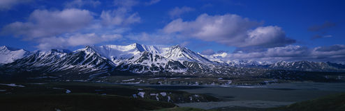 Alaska Range. This is a mountain scenic in an Alaska Range. The mountains are covered in snow with a blue sky and white puffy clouds Royalty Free Stock Photos