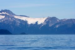 Alaska Sea and Mountains. Alaska shorline with snow-covered mountains in background royalty free stock photo