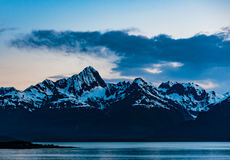 Alaska Sunset. Tracy Arm Fjord, AK, USA - May 27, 2016: Panorama of one of the many mountain peaks, islands and forest areas as seen while cruising the Tracy Arm stock photos