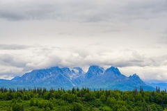 Alaska Talkeetna Mountain Range. Clouds hover over the peaks of Alaska`s Talkeetna Mountains.  Luscious summer green trees and brush in the foreground Royalty Free Stock Image