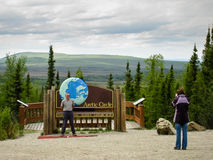 Alaska USA - Maj 29, 2009: Tecken för arktisk cirkel och turisterna Royaltyfri Foto