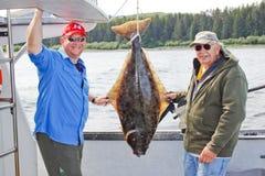 Alaska - viagem de pesca do alabote negro do filho do pai Imagens de Stock Royalty Free