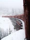 Alaska vit bergjärnväg i snö som korsar träbron Arkivbild