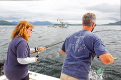 Alaska - Woman Catching Salmon. A photo of a woman fighting a pacific pink salmon as the captain assists while fishing the waters of the Inside Passage near Royalty Free Stock Photography