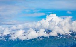 Alaskabo berg i moln under blå himmel Royaltyfri Foto