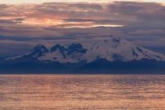 Alaskabo solnedgång som reflekterar i havet med berg och moln Arkivfoton