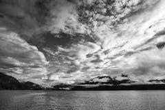 Alaskan Cloud Fandango. Dramatic clouds at sunset in Southeast Alaska in black and white Stock Image