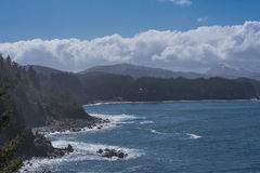 Alaskan Coastline. Pacific Ocean Crashing into Bluffs on the Alaskan Coast with Blue Skies and White Clouds in the Background Stock Image