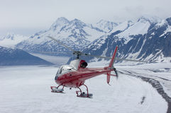 Alaskan Helicopter Series. A red and silver rescue helicopter flies across a remote glacier in Southeastern Alaska stock image