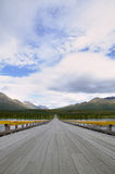 Vanishing Alaskan highway and glacial river bridge Stock Image