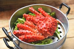 Alaskan King Crab Cooked steamer food on steaming pot seafood and lettuce vegetable on wooden background - red crab hokkaido royalty free stock image