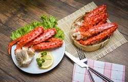 Alaskan King Crab Legs Cooked on white plate with lemon parsley lettuce vegetable and bamboo steamer on wooden background / red royalty free stock photo