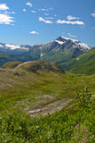 Alaskan Landscape. A photo of a snow capped mountain landscape  with blue sky and clouds. The photo was taken in Alaska and is in portrait vertical format Stock Photography