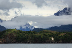 Alaskan lighthouse on side of mountains clouds drifting in Royalty Free Stock Images