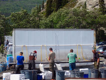 Alaskan residents cleaning their salmon during the subsistence fishing week in alaska. Alaskan residents utilizing a mobile cleaning station beside the copper Stock Images