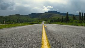 Alaskan Road. Driving along Top of the World Highway in Alaska royalty free stock image