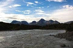 Alaskan Sediment River and Mountains. A river fed by heavily sedimented glacier runoff flows downstream between forest towards rugged snowcapped mountains, under Stock Photos