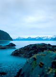 Alaskan Shoreline at Dawn. Rocks on the Alaskan shoreline with blurred water in early morning Royalty Free Stock Images