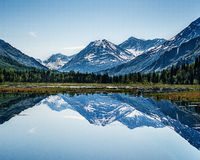 Alaskan Summer. A perfectly flat lake provides a flawless mirror to reflect the mountains of the Kenai peninsula Stock Images