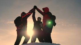 Alaskan travelers go to the top of a snowy hill and rejoice in victory against a winter sunset. team work of people stock video footage