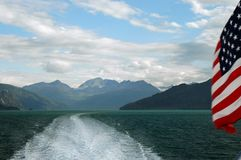 Alaskan Water Taxi And American Flag. Water taxi ride through Glacier Bay, Alaska with American flag waving on the side and view of the wake with mountains in Stock Photos