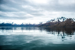 Alaskan Waters. Mountains from the Bay of Alaska. Cold waters, brooding skies Royalty Free Stock Photo