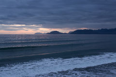 Alaskan Waves on Sunset. Lines of waves roll into Pasagshak Beach on Kodiak Island Alaska on sunset. A few surfers can be spotted waiting for the right wave Stock Photo