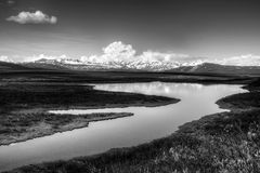 Alaskan wilderness in black and white. View of an Alaskan Lake in the interior in black and white with mountains in the distance and puffy clouds royalty free stock photos