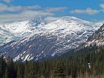 Alaskische Berge mit Wolken und Schnee Stockbild