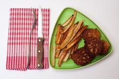 Albóndiga y patatas fritas en la placa con los utensilios en el kitc Imagenes de archivo