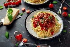 Albóndigas de las pastas de los espaguetis con la salsa de tomate, albahaca, queso parmesano de las hierbas en fondo oscuro imagen de archivo libre de regalías
