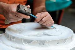 Albañil de piedra en el trabajo que talla un alivio ornamental Foto de archivo