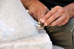 Albañil de piedra en el trabajo que talla un alivio ornamental Imagen de archivo libre de regalías